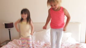 Two young girls bouncing excitedly. On bed looking at camera.Shot on Canon 5D Mk2 at at a frame rate of 30 fps stock video