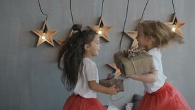 Two young girls - brunette and blonde hold Christmas gifts and have fun jumping on the bed near which hang on the wall. Wooden decorative stars with a bright stock video footage