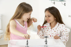 Two Young Girls Brushing Teeth at Sink Royalty Free Stock Image