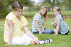 Two young girls bullying other young girl outdoors Stock Photo