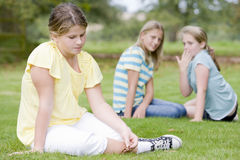 Two young girls bullying other young girl outdoors Stock Photos