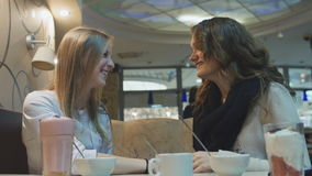 Two young girls in a cafe at a table and talk and laugh, share news. stock video footage