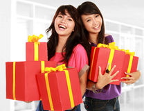 Two young girls carrying present Royalty Free Stock Images