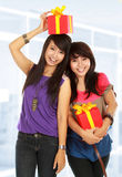 Two young girls carrying present Royalty Free Stock Photo