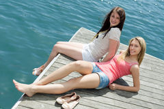 Two young girls in casual clothes sunbathing stock image
