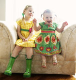 Two young girls on chair. Two happy, young girls in pretty dresses, sitting in a large easy chair Royalty Free Stock Photo