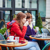 Two young girls chatting in a Parisian street cafe Royalty Free Stock Images