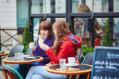Two young girls chatting in a Parisian street cafe Royalty Free Stock Photo