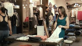 Two young girls choose clothes in shop. Two young girls make shopping stock footage
