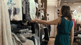 Two young girls choose clothes in shop. Two young girls make shopping stock video