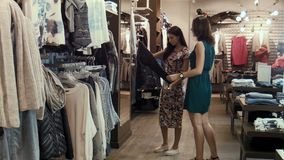 Two young girls choose clothes in shop. Two young girls make shopping stock video footage