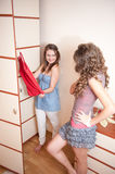 Two young girls choosing dress Stock Images