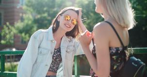 Portrait of two happy girls discussing latest gossip news. Two young girls in a city enjoying summer. Positive face expressions, emotions, feelings, body Royalty Free Stock Images