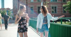 Portrait of two happy girls discussing latest gossip news. Two young girls in a city enjoying summer. Positive face expressions, emotions, feelings, body Royalty Free Stock Photography
