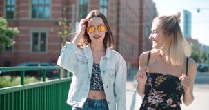 Portrait of two happy girls discussing latest gossip news. Two young girls in a city enjoying summer. Positive face expressions, emotions, feelings, body Stock Photo