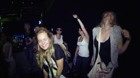 Two young girls clapping in crowded nightclub at rock party. Illumination. Spotlights. Shake head. Raise hands stock footage