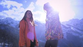 Two young girls climb the mountains in winter. Smiling and waving. Enjoy the winter mountain holiday. Have fun in the. Winter ski resort. Sunny day, behind the stock video