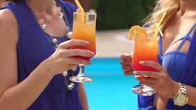 Close-up of two girls clink cocktail by the pool. Two young girls clink glasses with a refreshing cocktail with ice on a background of pool, close-up. Slow stock video footage