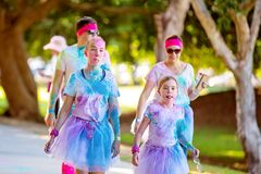 Two Young Girls In Costume Walk In Color Frenzy Fun Run. MACKAY, QUEENSLAND, AUSTRALIA - JUNE 2019: Two unidentified young girls covered in colored powder walk stock photography