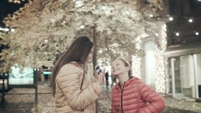 Two young girls dance in the autumn evening along the street. Two young girls listen to music on headphones in the. Two young girls listen to music on headphones stock video footage