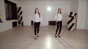 Two young girls are dancing in the dance studio. Evening dance rehearsal. HD stock video