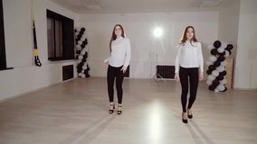 Two young girls are dancing in the dance studio. Evening dance rehearsal. HD stock video footage
