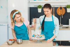 Two young girls decorating cup cakes with fruit. Baking delicious desserts at modern light kitchen in blue dickeys Stock Photo