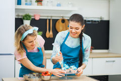 Two young girls decorating cupcakes with creme. Two young girls in modern kitchen decorating cupcakes with creme using baking tools Stock Photo