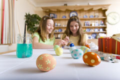Two young girls decorating Easter eggs Stock Photography