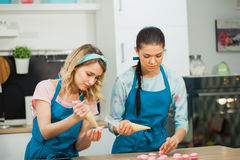 Two young girls decorating macaroons with piping bag filled with. Cream cheese. Baking traditional French dessrt Royalty Free Stock Photography