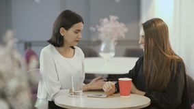 Two young girls discuss the clothes in cafe. Young attractive workers sit in the co-working space at the table. Handsome women sit at the cafe at work. Pretty stock video footage