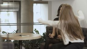 Two young girls discussing something looking at the smartphone. Young attractive woman sits in the co-working space at the table. Young cute woman worker has a stock video