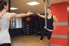 Two young girls do fly yoga and stretches in the studio. Royalty Free Stock Photo