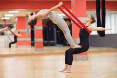 Two young girls do fly yoga and stretches in the studio Stock Photo
