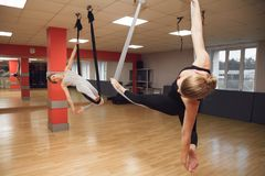 Two young girls do fly yoga and stretches in the studio. Stock Images