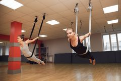 Two young girls do fly yoga and stretches in the studio. Stock Photo