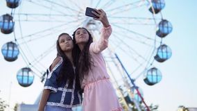 Two young girls do selfie using smartphone while standing on the background of a Ferris wheel. slow motion. Two beautiful young girls doing selfie using a stock footage