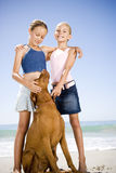 Two young girls and a dog on the beach Stock Photography
