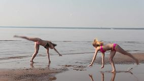 Two young girls doing acrobatics on the beach stock video