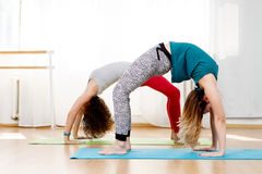 two girls doing yoga stretching in fitness class stock