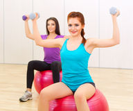 Two young girls doing gymnastic exercises Royalty Free Stock Photography