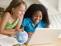 Two Young Girls Doing Their Homework On A Laptop. Smiling Stock Photos
