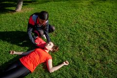 Two young girls practicing cardiopulmonary resuscitation manoeuvres in an open-air park. Two young girls dressed in sport clothes practicing cardiopulmonary royalty free stock images