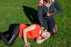 Two young girls practicing cardiopulmonary resuscitation manoeuvres in an open-air park. Two young girls dressed in sport clothes practicing cardiopulmonary royalty free stock photos
