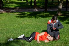 Two young girls practicing cardiopulmonary resuscitation manoeuvres in an open-air park. Two young girls dressed in sport clothes practicing cardiopulmonary stock photo