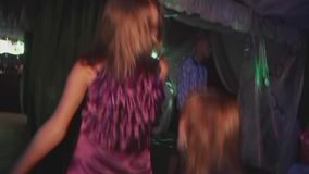Two young girls in dresses dance in nightclub without shoes. People. Smiling. Cheering. Night party. Discotheque. Entertainment stock video