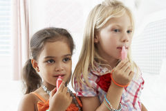 Two Young Girls Dressing Up And Putting On Make Up Together Stock Photography