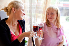Two young girls are drinking wine. In cafe Royalty Free Stock Image