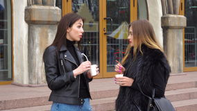 Two young girls drinks coffee and talks. Two young beautiful girls drinks coffee and talks on the street stock video