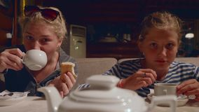 Two young caucasian girls drink tea and joke in cafe in evening after a hike. Two young girls drinks tea in cafe in evening after a hike stock video footage